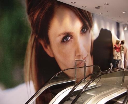 Pose d'un visuel adhésif grand format sur le mur d'un magasin.