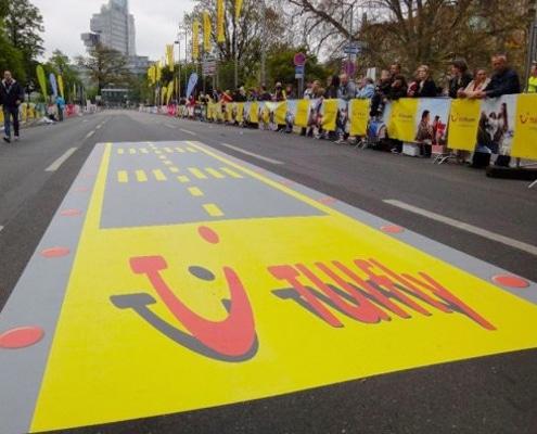 Impression de banderole publicitaire et d'adhésif sol pour un événement sportif.