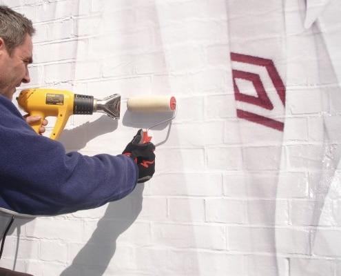 Nos poseurs d'adhésif spécialisés appliquent de l'adhésif spécial mur pour une communication grand format.