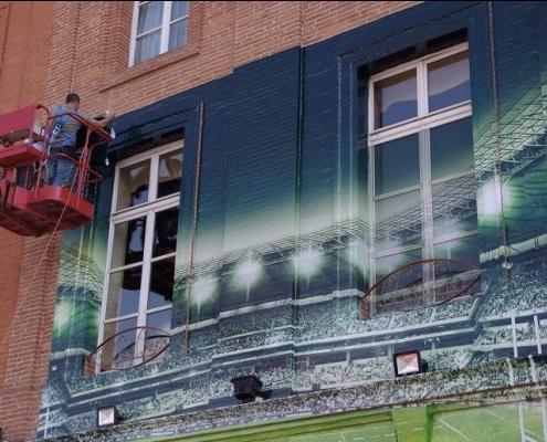 Pose d'adhésif spécial mur brut pour former une fresque murale géante.