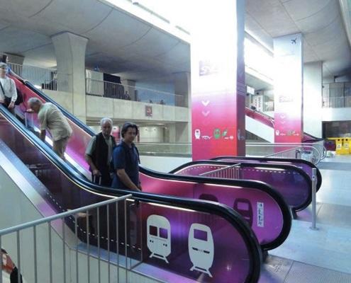 Pose d'adhésif coloré transparent sur un escalier mécanique.